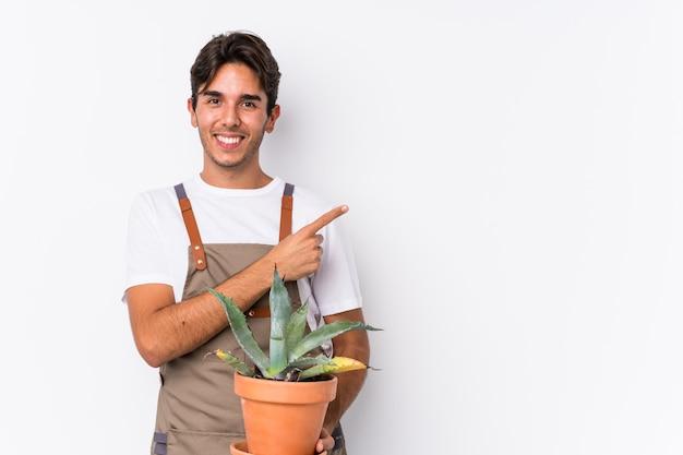 O homem caucasiano novo do jardineiro que guarda uma planta isolou o sorriso e apontar de lado, mostrando algo no espaço em branco.