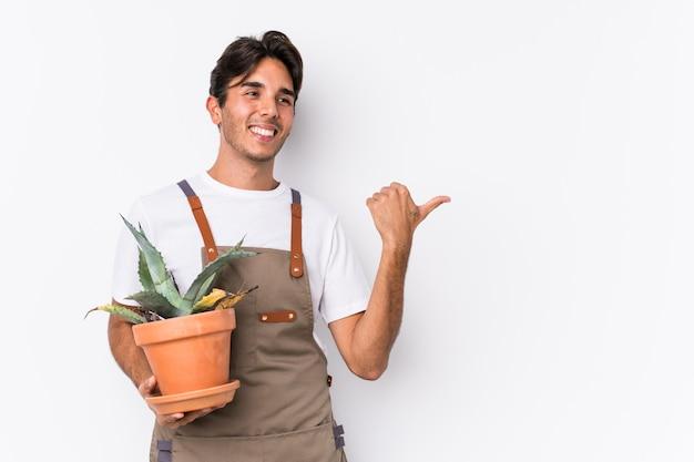 O homem caucasiano novo do jardineiro que guarda uma planta isolou pontos com o dedo do polegar afastado, rindo e despreocupado.