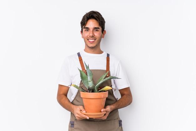 O homem caucasiano novo do jardineiro que mantém uma planta isolou feliz, sorridente e alegre.