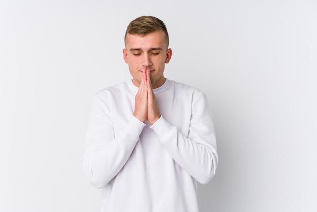 O homem caucasiano novo na parede branca que guarda as mãos reza perto da boca, sente-se confiante.