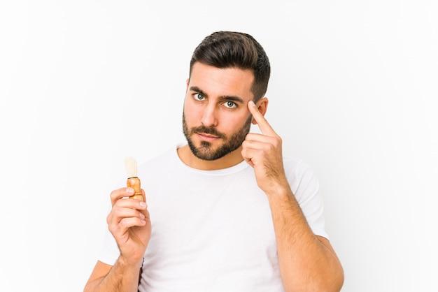 O homem caucasiano novo que barbeia recentemente isolado apontando seu templo com o dedo, pensando, focalizado em uma tarefa.