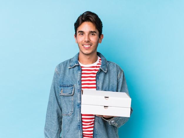 O homem caucasiano novo que guarda pizzas isolou feliz, sorrindo e alegre.