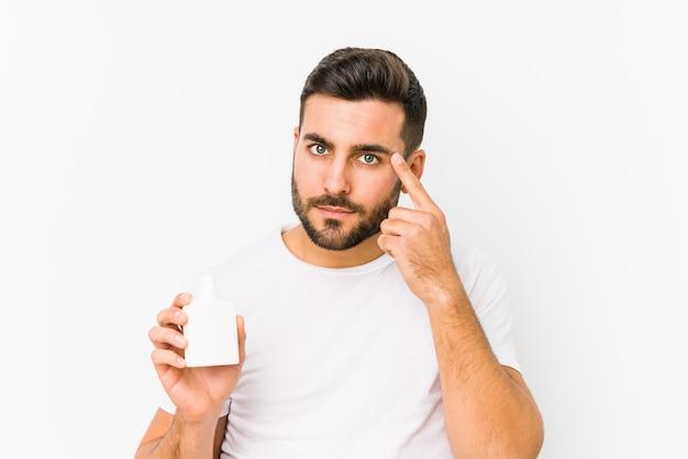 O homem caucasiano novo que guarda uma garrafa das vitaminas isolou apontar seu templo com o dedo, pensando, focalizado em uma tarefa.