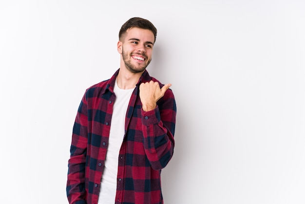 O homem caucasiano novo que levanta em uma parede branca isolou pontos com o dedo do polegar afastado, rindo e despreocupado.