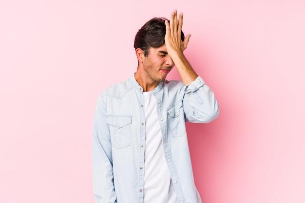 O homem caucasiano novo que levanta em uma parede cor-de-rosa isolou esquecendo algo, batendo na testa com palma e fechando os olhos.
