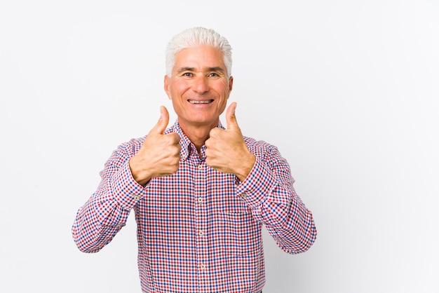 O homem caucasiano sênior isolado com polegares levanta, felicidades sobre algo, apoia e respeita o conceito.