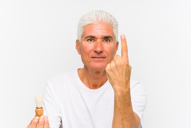 O homem caucasiano sênior raspou recentemente mostrando o número um com o dedo.