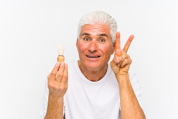 O homem caucasiano sênior raspou recentemente mostrando o sinal da vitória e sorrindo amplamente.