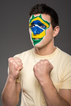 O homem cerrou os punhos e torceu para o brasil.