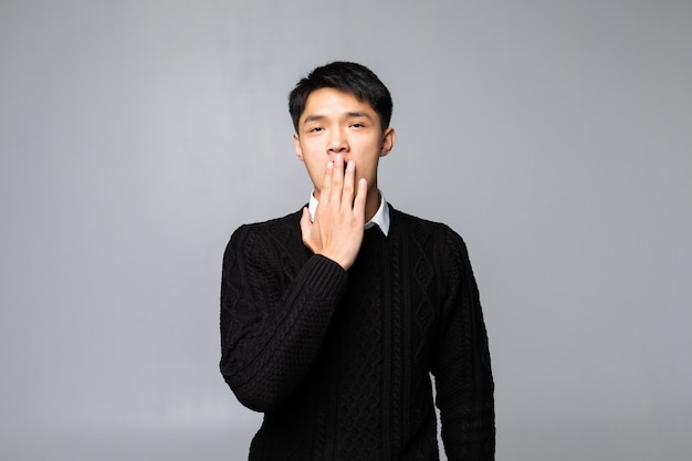 O homem chinês novo chocou a boca de coberta com as mãos para o erro que está sobre a parede branca isolada. conceito secreto.