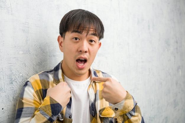 O homem chinês novo enfrenta o close up surpreendido, sente bem sucedido e próspero