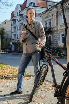 O homem com a bicicleta e uma bebida