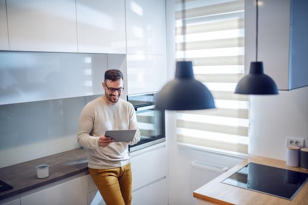 O homem com barba caucasiano caucasiano de sorriso considerável vestiu-se ocasional e com os óculos que inclinam-se no balcão de cozinha e que usa a tabuleta.