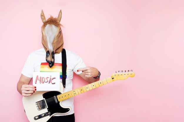O homem com máscara de cavalo e guitarra elétrica aponta para uma placa que diz música