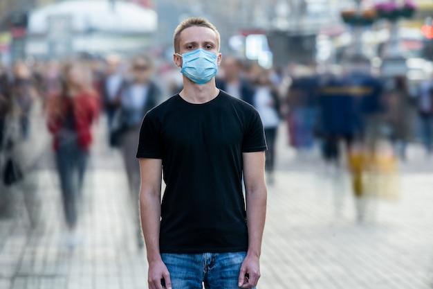 O homem com máscara médica no rosto está parado no meio de uma rua urbana