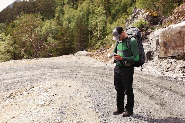 O homem com mochilas verifica seu telefone em pé na estrada