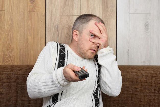 O homem com o controle remoto com medo de assistir ao noticiário