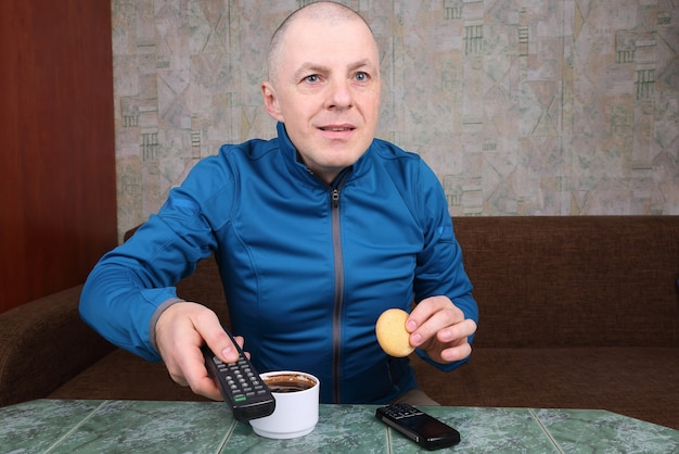 O homem com o controle remoto da tv na mão, bebendo café e assistindo a um programa de tv