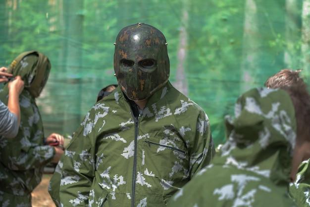 O homem com roupas e máscara para airsoft. homem militar