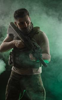O homem com roupas especiais militares posando com uma arma nas mãos em um fundo escuro na névoa