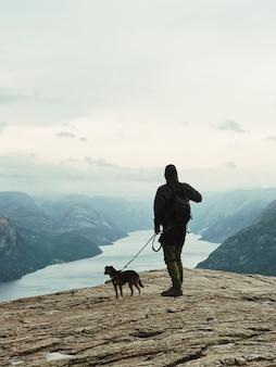O homem com um cachorro está parado antes da bela paisagem
