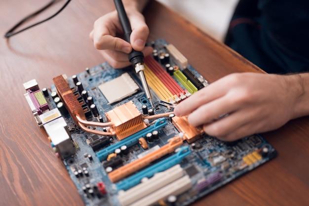 O homem com um ferro de solda repara o material informático.