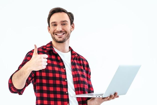 O homem com um laptop em pé sobre o fundo branco