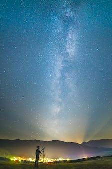 O homem com uma câmera fica no fundo do céu estrelado. período noturno