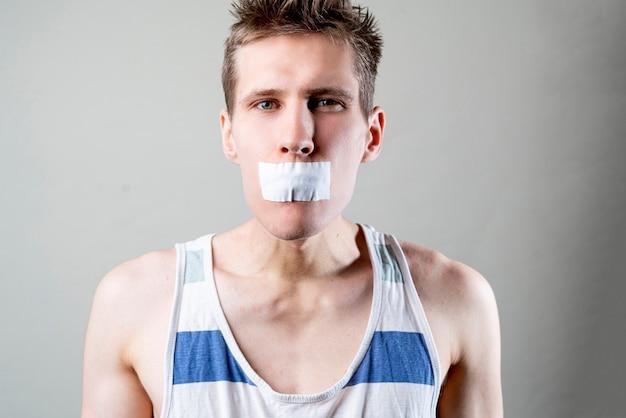 O homem com uma fita fecha a boca, para de falar e fecha, conceito de censura,