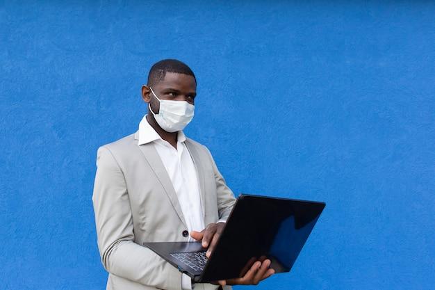 O homem com uma máscara protetora com um laptop na mão