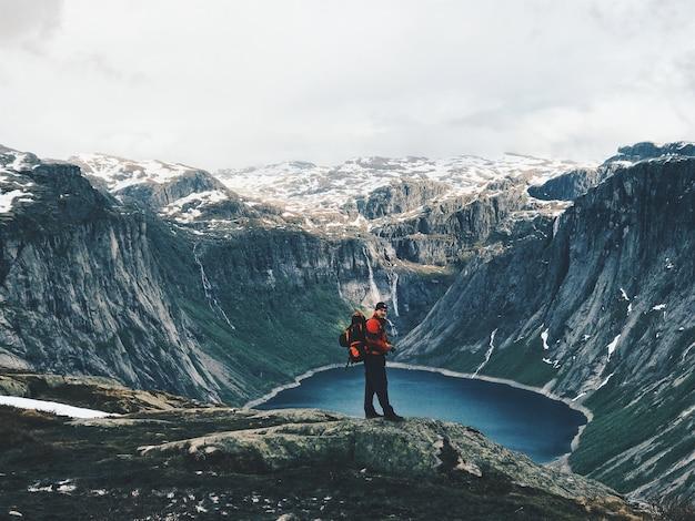 O homem com uma mochila admira a deslumbrante paisagem da montanha