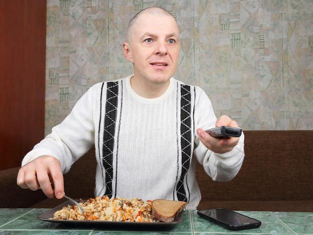 O homem come pilaf de arroz e assiste ao programa de tv