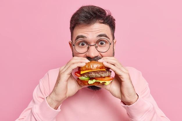 O homem come um hambúrguer delicioso e avarento, sente muita fome, consome fast food, usa óculos redondos e suéter