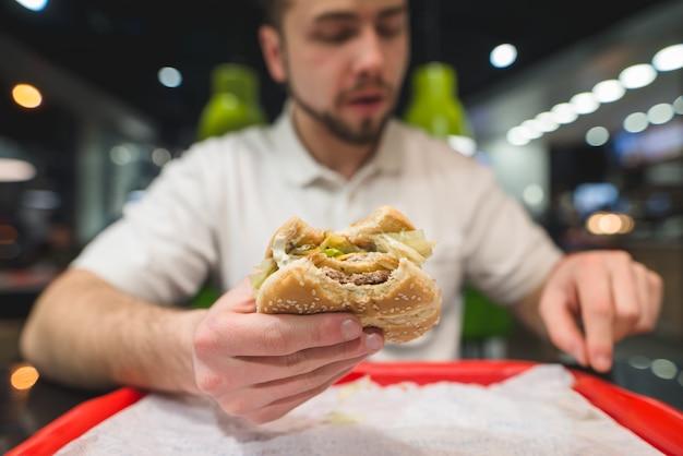 O homem come um ótimo e delicioso hambúrguer. concentre-se no hambúrguer. fast-food no restaurante.