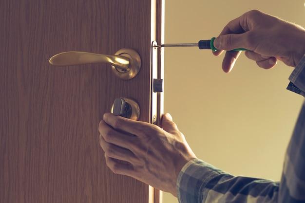 O homem conserta o chaveiro e coloca a porta na porta de madeira.