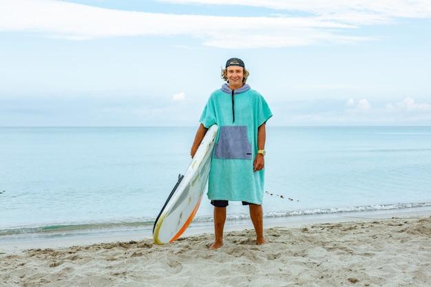 O homem considerável anda com prancha em branco branca espera a onda surfar o ponto na costa do oceano do mar.