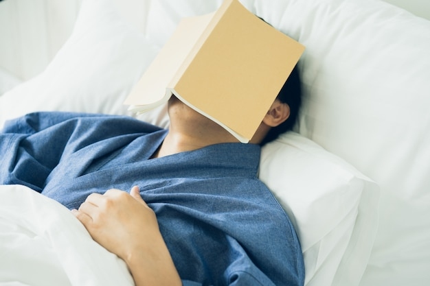 O homem considerável asiático leu livros ao dormir. capa para livro de homem sonolência