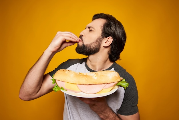 O homem considerável com sanduíche grande faz o gesto delicioso.