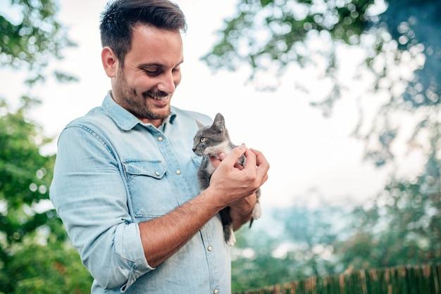 O homem considerável é de terra arrendada e de aperto o gato bonito fora.