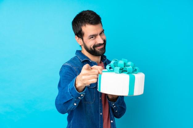 O homem considerável novo com um bolo grande sobre a parede azul isolada aponta o dedo em você com uma expressão confiante