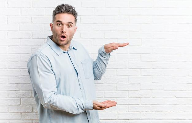 O homem considerável novo contra uma parede de tijolos chocou e surpreendeu guardarando um copyspace entre as mãos.