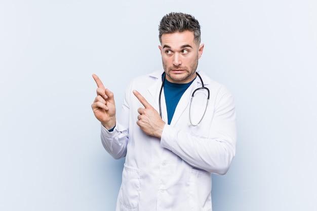 O homem considerável novo do doutor chocou apontar com os indicadores a um copyspace.
