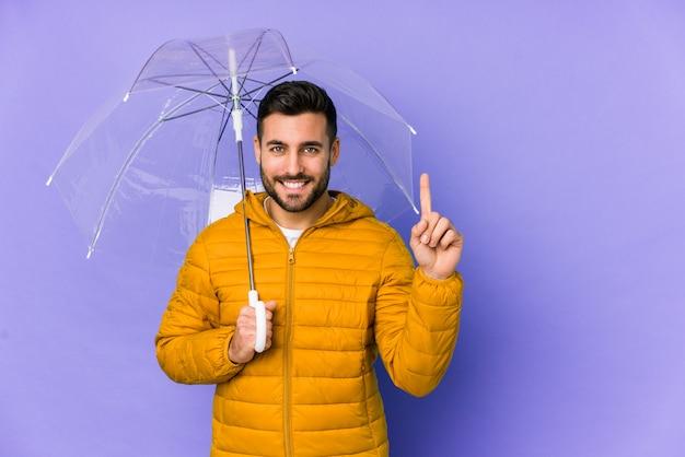 O homem considerável novo que guarda um guarda-chuva isolou mostrar o número um com dedo.