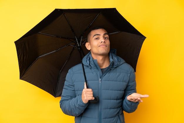 O homem considerável novo que guarda um guarda-chuva sobre a parede amarela isolada que faz dúvidas gesticula ao levantar os ombros