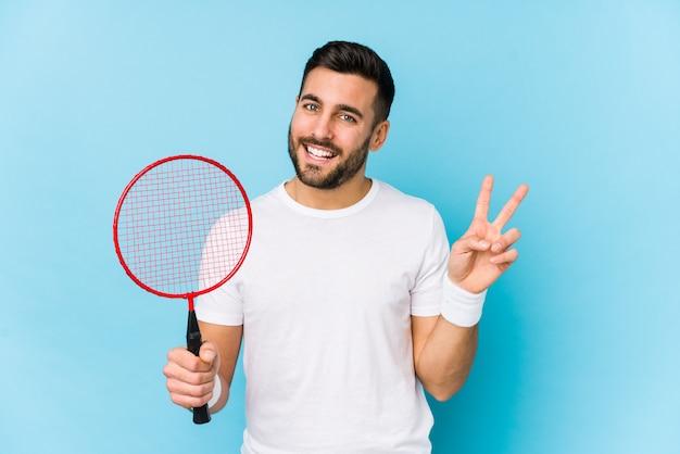 O homem considerável novo que joga o badminton isolou alegre e despreocupado mostrando um símbolo de paz com os dedos.