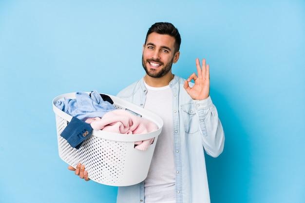O homem considerável novo que lava a roupa isolou mostrar alegre e seguro mostrando o gesto aprovado.
