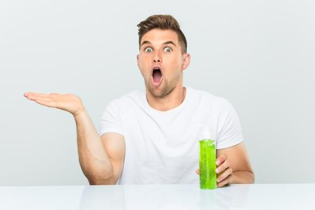 O homem considerável novo que prende uma garrafa de aloe vera imprimiu guardar o espaço da cópia na palma.