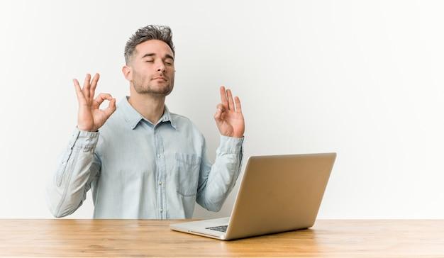O homem considerável novo que trabalha com seu portátil relaxa após o dia de trabalho duro, está executando a ioga.