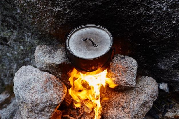 O homem construiu uma fogueira na floresta na natureza. sobreviver nas montanhas