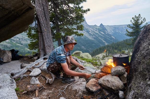 O homem construiu uma fogueira na floresta na natureza. sobreviver